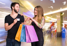 Happy couple with shopping bags in the mal Stock Photos