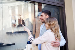Happy couple with shopping bags at shop window Royalty Free Stock Photos