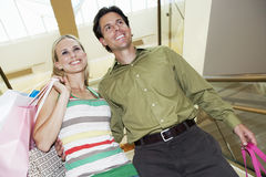 Happy Couple With Shopping Bags On Staircase Royalty Free Stock Photography