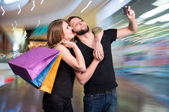 Happy couple with shopping bags taking selfie. On a blue background stock photo