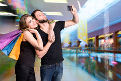 Happy couple with shopping bags taking selfie. In the mall royalty free stock images