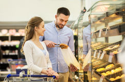 Happy couple with shopping cart at grocery store Royalty Free Stock Photo