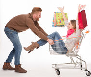 Happy couple with shopping cart Royalty Free Stock Photo