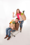 Happy couple with shopping cart Stock Photography