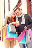 Happy couple shopping in the city with smartphone Stock Image