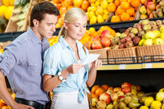 Happy couple with shopping list against the heaps of fruits Royalty Free Stock Images