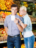 Happy couple with shopping list against the piles of fruits Stock Images