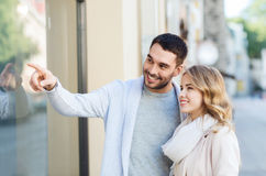 Happy couple shopping and looking at shop window Stock Image
