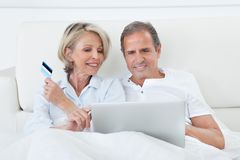 Happy couple shopping online Stock Photos