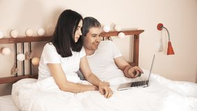 Happy couple shopping online using their laptop in bed at home stock footage