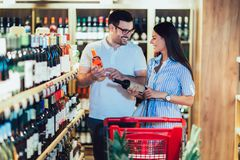 Couple shopping in supermarket buying wines stock image