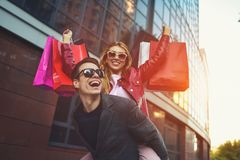 Couple in shopping together. Happy couple shopping together and having fun. Boyfriend carrying his girlfriend on the piggyback. Happy couple shopping together royalty free stock photos