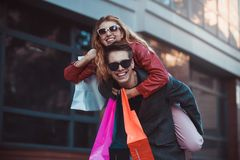 Couple in shopping together. Happy couple shopping together and having fun. Boyfriend carrying his girlfriend on the piggyback. Happy couple shopping together royalty free stock images