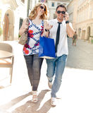 Happy Couple on Shopping Tour. Man holds a Mobile Phone to his ear Royalty Free Stock Images