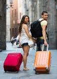 Happy couple in shorts walking through city. Happy couple in shorts with luggage walking through city street Stock Photo