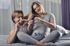 Happy couple showing hand shape heart for the future baby boy Royalty Free Stock Photo