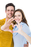 Happy couple showing a heart shape with their fingers Royalty Free Stock Images