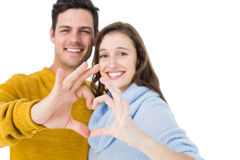 Happy couple showing a heart shape with their fingers Stock Photography