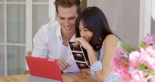 Happy couple showing off ultrasound pictures Stock Photo