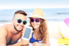 Happy couple showing smartphone at the beach royalty free stock images