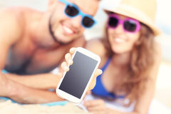 Happy couple showing smartphone at the beach royalty free stock photography