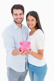Happy couple showing their piggy bank Royalty Free Stock Image