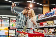 Happy couple showing thumbs up. While taking a selfie at supermarket Royalty Free Stock Photography