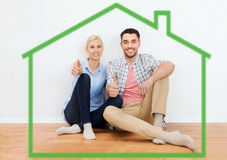 Happy couple showing thumbs up at new home. Home, people, accommodation, moving and real estate concept - happy couple sitting on floor and showing thumbs up at Royalty Free Stock Photo