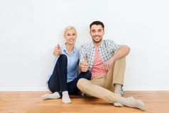 Happy couple showing thumbs up at new home. Home, people, repair, moving and real estate concept - happy couple sitting on floor and showing thumbs up at new Stock Images