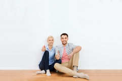 Happy couple showing thumbs up at new home. Home, people, repair, moving and real estate concept - happy couple sitting on floor and showing thumbs up at new Royalty Free Stock Photography
