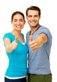 Happy Couple Showing Thumbs Up Sign. Portrait of happy couple showing thumbs up sign over white background. Vertical shot Stock Photo