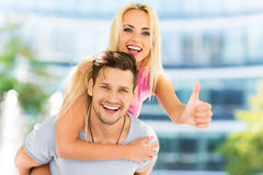 Happy couple showing thumbs up. Happy young couple outdoors, smiling Royalty Free Stock Images