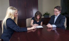 Happy couple signing documents with advisor Royalty Free Stock Photos