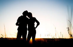 Happy couple silhouette on the meadow during sunset Stock Photos