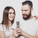 Happy couple singing in karaoke. Over white background Stock Images