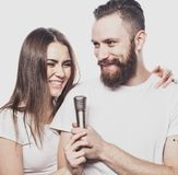Happy couple singing in karaoke over white background,. Lifestyle Stock Images