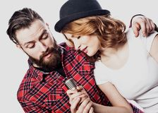 Happy couple singing in karaoke over white background,. Studio shoot Stock Image
