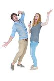 Happy couple singing into microphones Royalty Free Stock Images