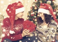 Happy couple sit near christmas tree and decoration at home. Winter holiday and love concept. Yellow toned with snow. Stock Photo