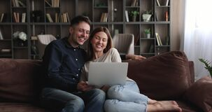 Happy cheerful couple use laptop greeting friend making video call