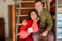 Happy couple sit on the stairs background of the new apartment. stock photo