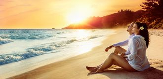 Happy Couple Sits on the Ocean Coast. At Sunset. Summer Vacation stock photo