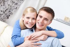 Happy couple sits on the sofa. Hugging each other Stock Photography