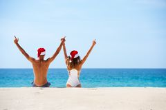 Happy couple sits white beach in christmas hats stock photography