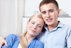 Happy couple sits on the white couch Stock Photography