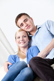 Happy couple sits on the white leather sofa Stock Photos