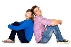 Happy couple sitting back to back. Young couple over white background Stock Image