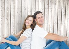 Happy couple sitting back to back. Against wooden background Royalty Free Stock Photo