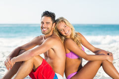 Happy couple sitting back to back on beach. On a sunny day Royalty Free Stock Photography