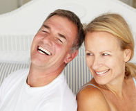 Happy couple sitting back to back on bed. Smiling at each other Stock Photography